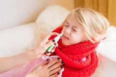 照顾对待她的儿童` s流鼻水与鼻孔喷射 免版税库存图片