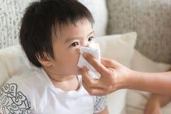照顾帮助吹与纸组织的亚洲儿童` s鼻子 海 免版税库存照片