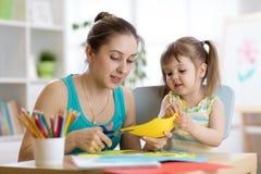 照顾帮助她的孩子切开色纸 免版税库存照片