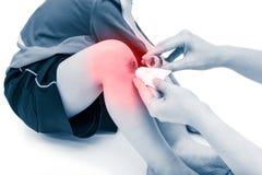 照顾干净并且提供紧急救护在创伤在儿子腿以红色 免版税图库摄影
