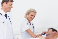 照顾患者的微笑的医疗队 库存照片