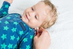照顾手清洁有棉花棒的婴孩耳朵 免版税库存照片