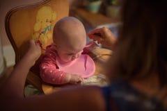 照顾把围嘴放在婴孩上在高脚椅子 库存图片