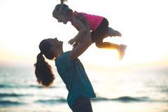 照顾投掷的孩子她的空气的在海滩的日落 免版税库存照片