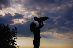 照顾抱着天空背景的一个婴孩 母亲和儿子 愉快的系列 免版税库存图片