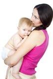 照顾抱着她的胳膊的一个赤裸婴孩 免版税库存图片