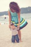 照顾抱着第一步的婴孩在海滩 库存照片