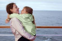 照顾拥抱在船甲板的女儿  库存照片