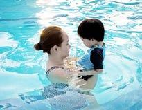 照顾拥抱她的游泳池的儿子在日落:软的fo 图库摄影