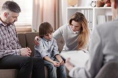 照顾拥抱她的自我中心儿子,坐在他的父亲duri旁边 免版税库存照片