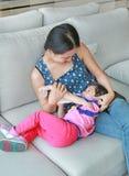 照顾拥抱她逗人喜爱的亚洲儿童女孩年龄大约一岁和九个月喝从在沙发的一个瓶 库存图片