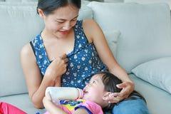 照顾拥抱她逗人喜爱的亚洲儿童女孩年龄大约一岁和九个月喝从瓶 库存照片