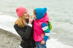 照顾拥抱小女儿,并且乐趣手指接触她的鼻子在海边 免版税库存照片