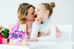照顾拥抱有明信片的女儿在前景,愉快的母亲 库存图片