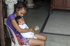 照顾拥抱的婴孩在教会门门乞求为施舍 库存照片