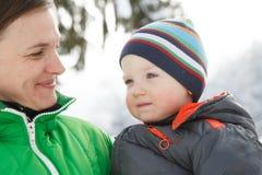 照顾拿着她的一个多雪的冬天风景的儿子 库存照片