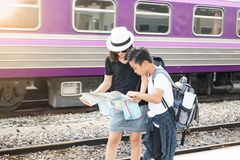 照顾拿着寻找旅行的地图和儿子乘火车 库存图片