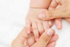 照顾按摩她的婴孩的手的手 免版税图库摄影