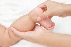 照顾按摩她的婴孩的腿和脚肌肉的手 库存照片