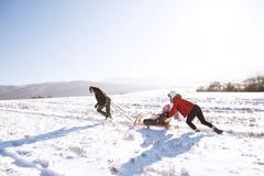 照顾推挤爬犁的,拉扯她的父亲女儿 冬天na 图库摄影