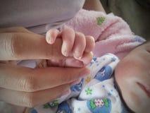 照顾握她的婴孩的手新出生与软的焦点 免版税库存图片