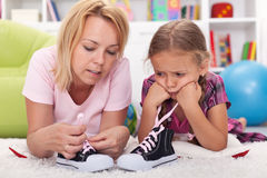 照顾教的小女孩附加她的鞋子 免版税库存图片