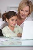教她的小女孩的母亲 免版税库存照片