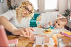 照顾显示婴孩在巧妙的电话的有趣的录影 免版税库存照片