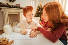照顾有信件的帮助的可爱的儿子给圣诞老人 库存照片