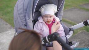 照顾有橙色匙子的,坐在婴儿推车的孩子哺养的婴孩房子外 股票录像