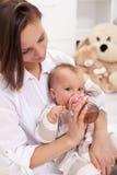 照顾有瓶的提供的女婴 库存图片