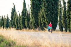 照顾有跑步在日落风景的婴儿车的赛跑者 库存图片