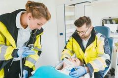照顾有鞭打的受伤的妇女的军医在救护车 免版税库存照片