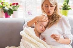 照顾检查温度她病的矮小的女儿 免版税库存照片