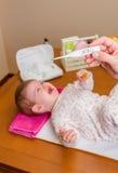 照顾测量温度婴孩的手  库存图片