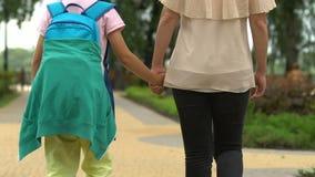 照顾用手拿着儿子,走到为第一次的学校,令人鼓舞孩子 股票录像