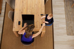 照顾研究有坐由桌的婴孩的膝上型计算机 库存照片