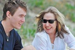 照顾笑的微笑的爱分享时间与儿子夏天海滩假日 免版税库存图片