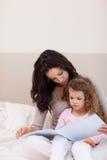 照顾读她的小女儿的一个故事 库存图片