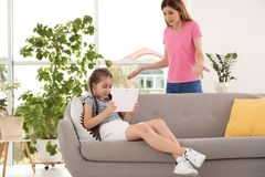 照顾责骂孩子,当她使用片剂在家时 免版税库存图片