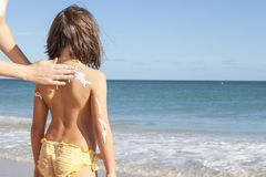 照顾适用于sunblock奶油她的女儿后面 库存照片