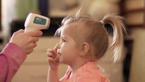 照顾采取女儿` s温度使用一个数字体温计户内在4k 股票录像
