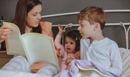 照顾阅读书给她的儿子在床上 免版税库存图片