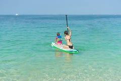 照顾,并且坐他可爱的矮小的女儿站立委员会获得乐趣在夏天海滩假期时 库存照片