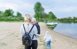 照顾,并且她的两个孩子沿美丽如画的河岸走 图库摄影