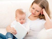 照顾读书一个小婴孩在沙发 库存图片