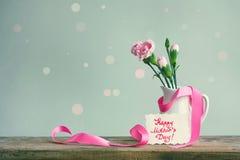 照顾` s天卡片,在一个白色花瓶的桃红色康乃馨有丝带的 库存照片