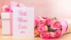 照顾` s天礼物、桃红色玫瑰和最佳的妈妈贺卡在桌上 库存图片