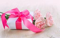照顾` s天背景,白色礼物盒,三支桃红色康乃馨 库存照片