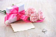 照顾` s天背景,礼物盒,三支桃红色康乃馨,纸 免版税库存图片